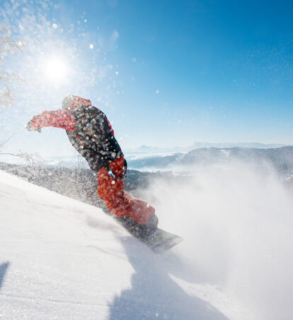 Freerider snowboarder riding the slope on a sunny winter day in the mountains copyspace snowboarding active lifestyle sports recreation resort. Snow in the air