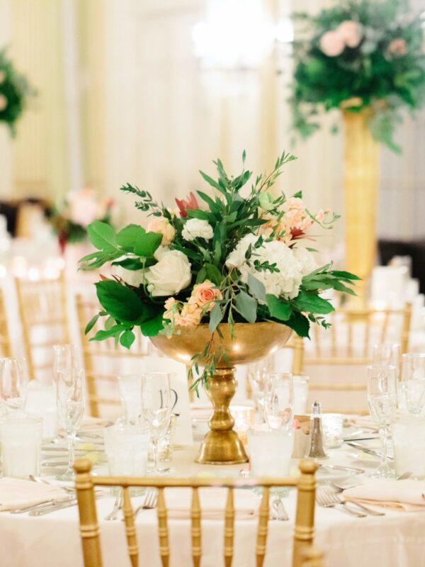 set tables in a ballroom for a wedding