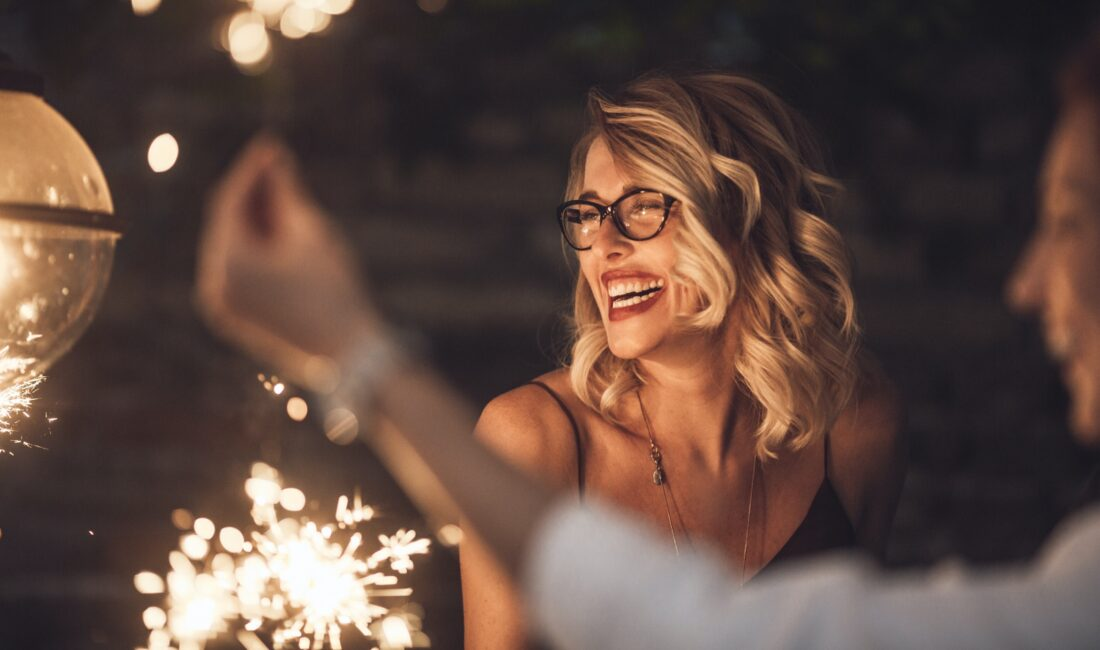 Woman laughing amid fireworks