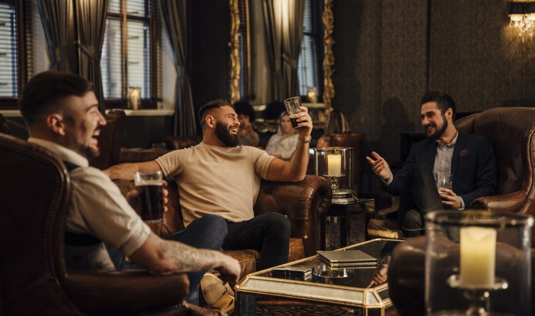 Men sitting in a lounge area drinking and laughing