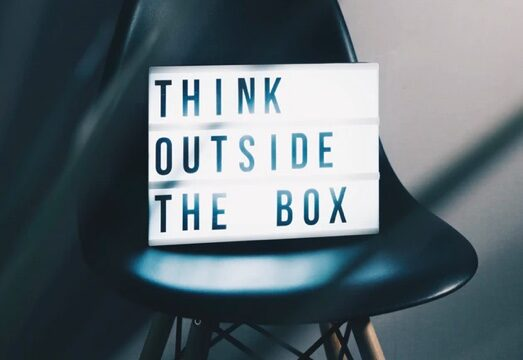"Sign saying ""Think Outside the Box"" sitting on a chair"