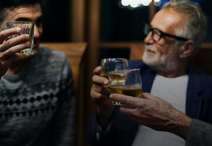 Men in a bar toasting with whiskey glasses