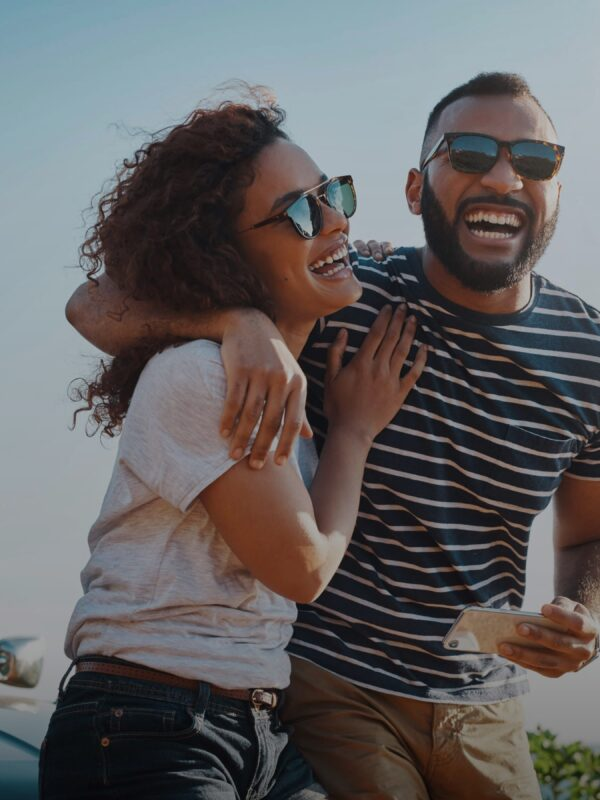 Couple laughing and hugging next to a car on the beach