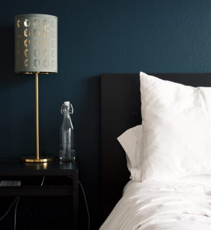 hotel bed and bedside table with a lamp and glass bottle of water