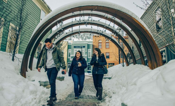 Three people walking under snow-covered arches
