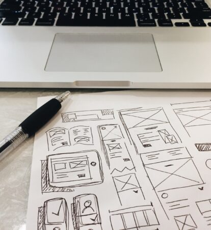 laptop and sketches of website design on a desk